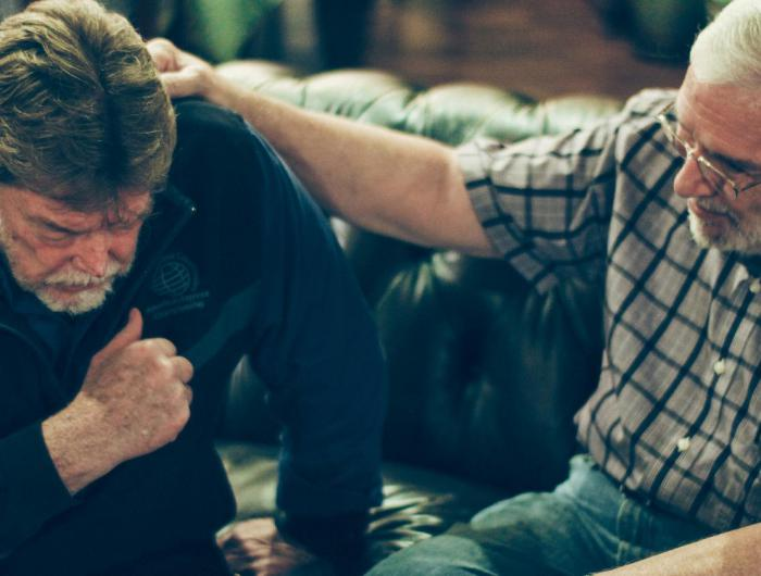 men praying for each other